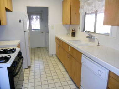 Galley kitchen with gas stove, dishwasher, tile counter tops and refrigerator.