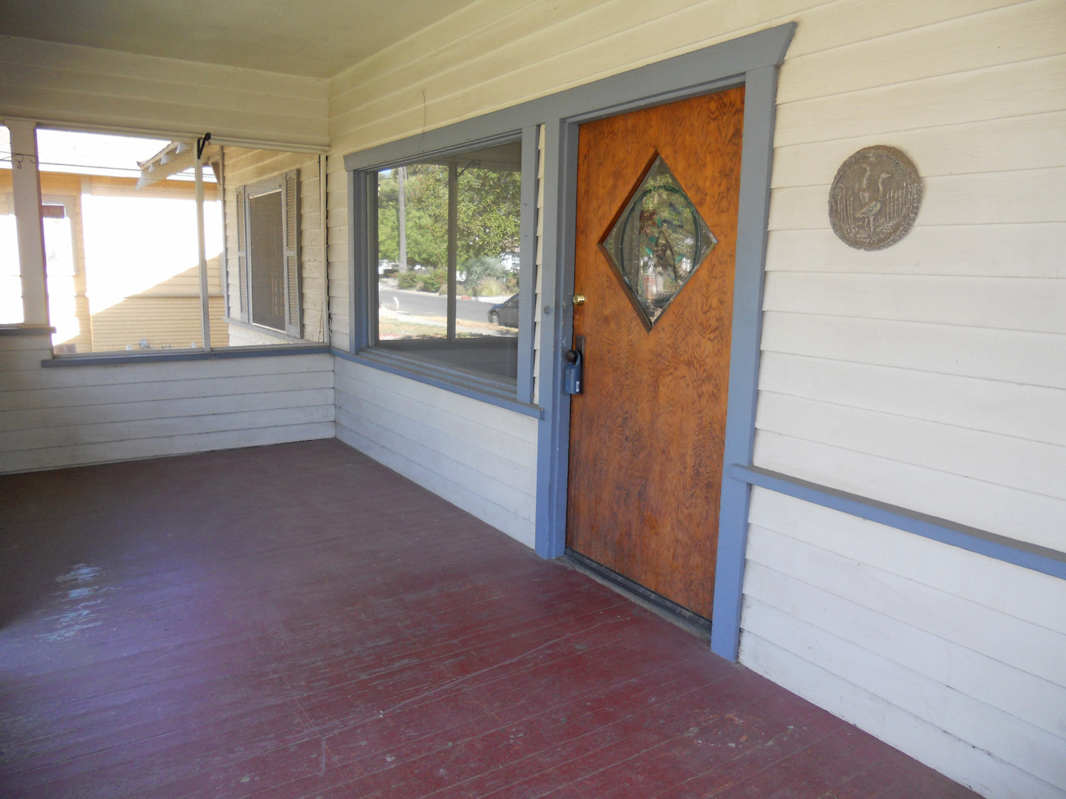 Large front porch with original front door and large windows.