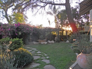 Sunset view of intimate backyard which was completely redone with a bougainvillea-covered pergola, gas fire pit and real boulders that were shipped to this location to be used as seats.
