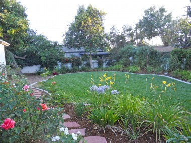 View of serene backyard from patio, showing the pathway which leads to the back sitting area underneath the avocado tree.