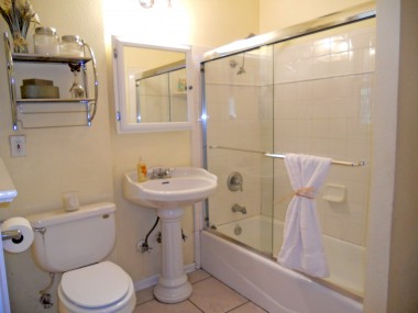 Remodeled bathroom with tile floor and pedestal sink.