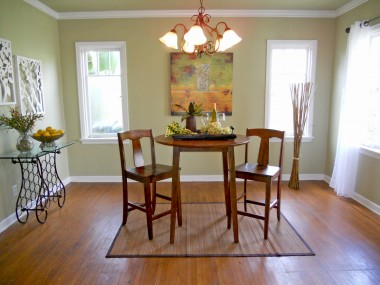 Formal dining room with hardwood floors, base boards and crown molding.