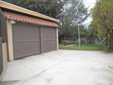2-car detached garage with new roof leading to the pool-sized backyard that has mature trees that offer privacy and peaches and citrus. The garage door has been painted since this photo was taken.