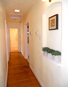 Hallway with hardwood floors and alcove for paintings or knick knacks.