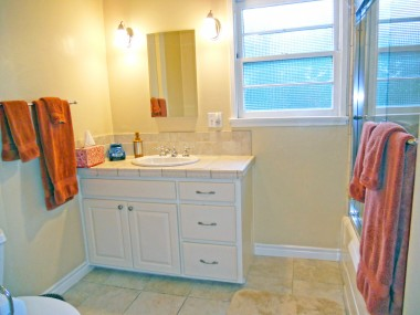 Remodeled hallway bathroom with tile floor and glass shower doors.