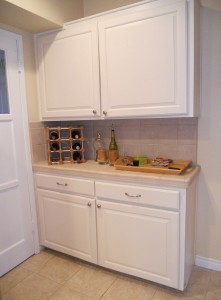 More remodeled kitchen cabinetry, with door to left leading to separate laundry room.