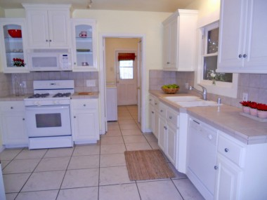 Remodeled kitchen with tile counters, tile floors, dishwasher and nook area for small table and chairs.