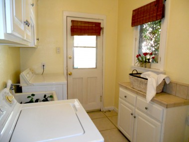 Separate indoor laundry room with lots of cabinetry, utility sink, washer/dryer, and built-in ironing board.