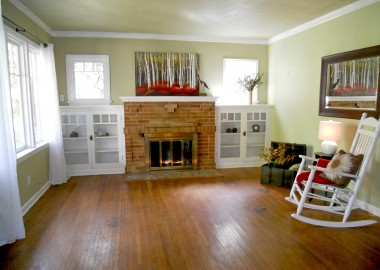 Living room with hardwood floors, glass cabinetry flanking the original fireplace, crown molding and baseboards.