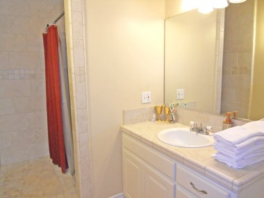 Remodeled private master bathroom with tiled shower enclosure, as well as separate toilet room.