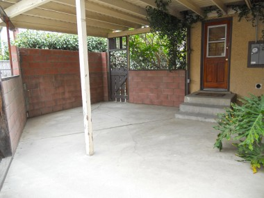 Large covered patio with gate leading to the side yard.