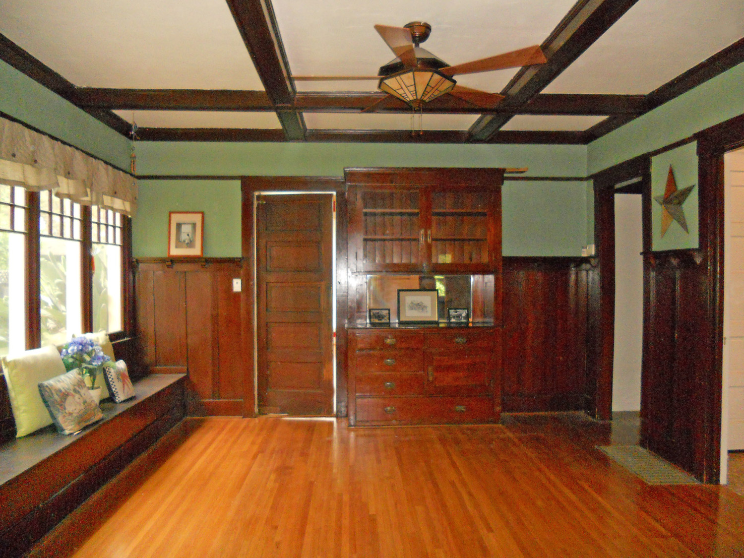 Formal dining room with plate rails, coffered ceiling, built-in hutch, large window seat and gorgeous original windows!