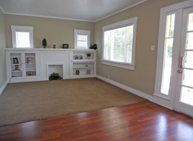 Living room with faux fireplace and built-in display shelves, newer double pane windows and horizontal privacy blinds.
