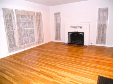 Spacious living room with fireplace. Original hardwood floors were recently professionally refinished.