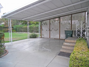 Covered patio off the back of the house, that was also utilized as a carport. Or set up a lovely table and chairs to enjoy overlooking the spacious backyard.