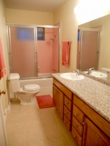 Partially remodeled bathroom with original tile in shower enclosure which looks new, tile floor is new, and the vanity is newer with granite counter top.