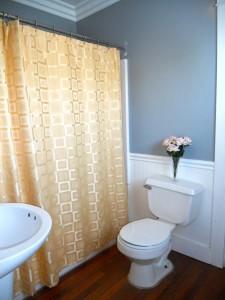 Full bathroom with shower in tub, newer pedestal sink, toilet, flooring and crown moulding.