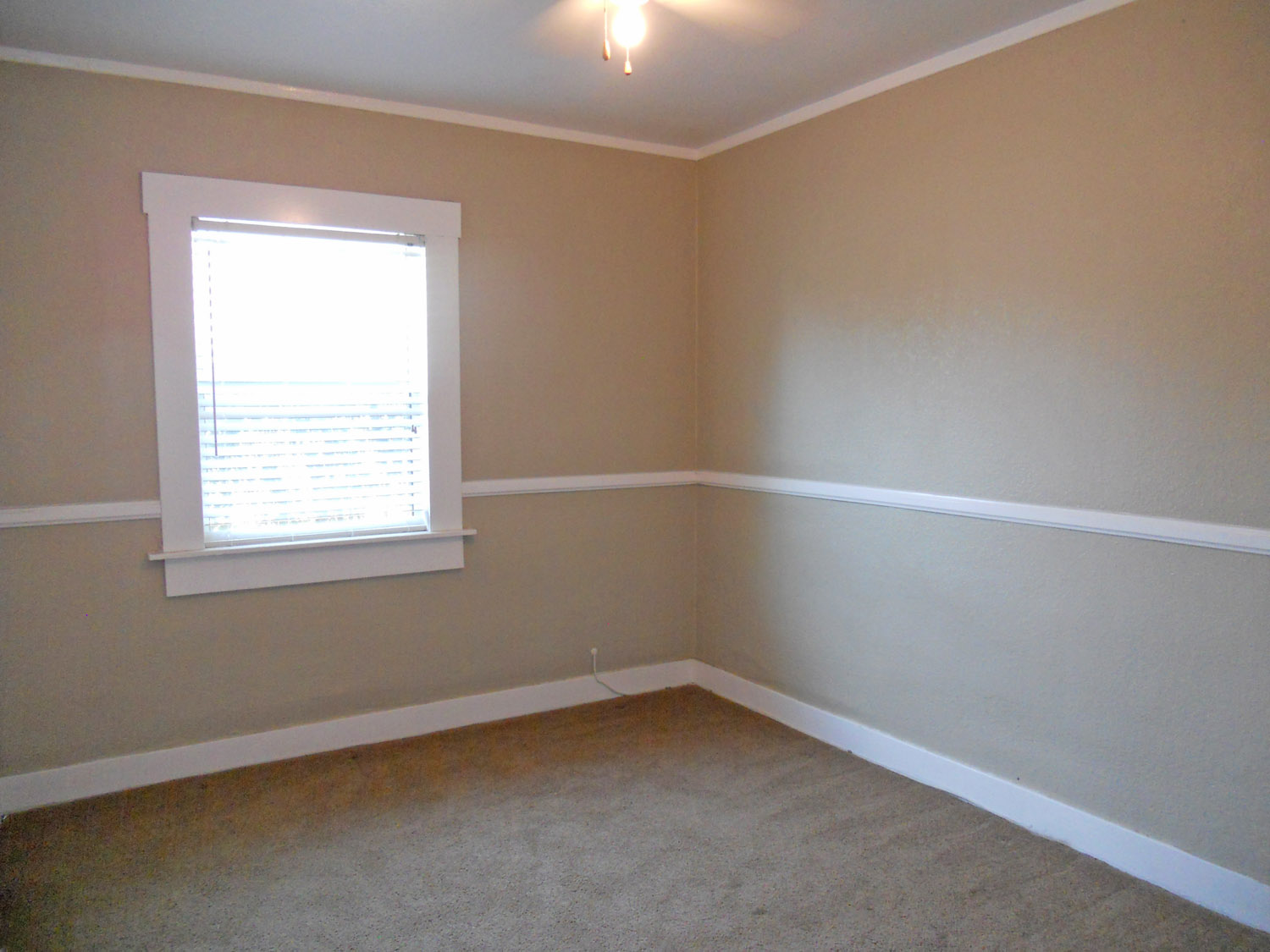 One of the bedrooms, with ceiling fan, newer double pane window, and carpeting.