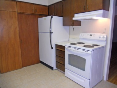 Alternate view of kitchen with refrigerator and newer stove (that both stay), along with a stackable washer/dryer unit that also stays.