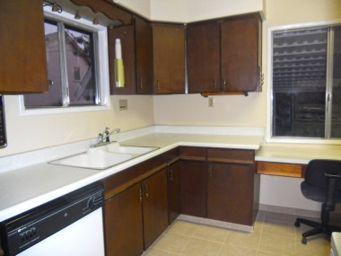 Dishwasher, newer tile floor, lots of cabinetry, and a desk in the bright kitchen.