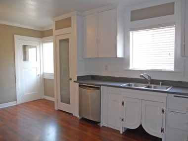 Kitchen with newer dishwasher and gas stove, glass door to pantry, newer sink, and doorway to separate laundry room.