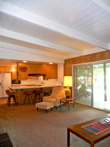 View of family room into the kitchen. Note the cathedral ceiling with wood beams.