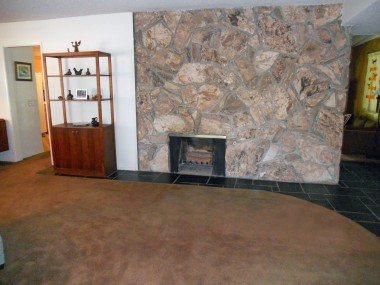 View of fireplace in formal living room.