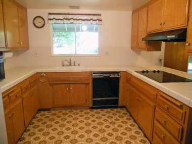 Kitchen with tiled counter tops, dishwasher, electric cook-top and double oven on other wall.