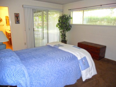 Master bedroom with private 3/4 bathroom and entry to back patio via sliding glass door.