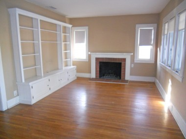 Living room with hardwood floors, fireplace and built-in shelving and TV alcove.