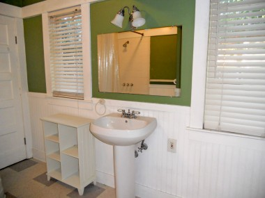 Alternate view of hallway bathroom with beadboard and pedestal sink.