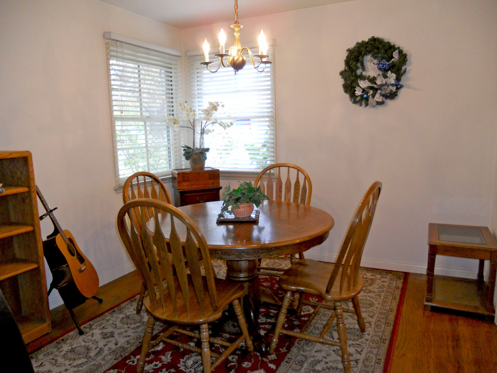 Formal dining room with hardwood floors and lovely corner windows.