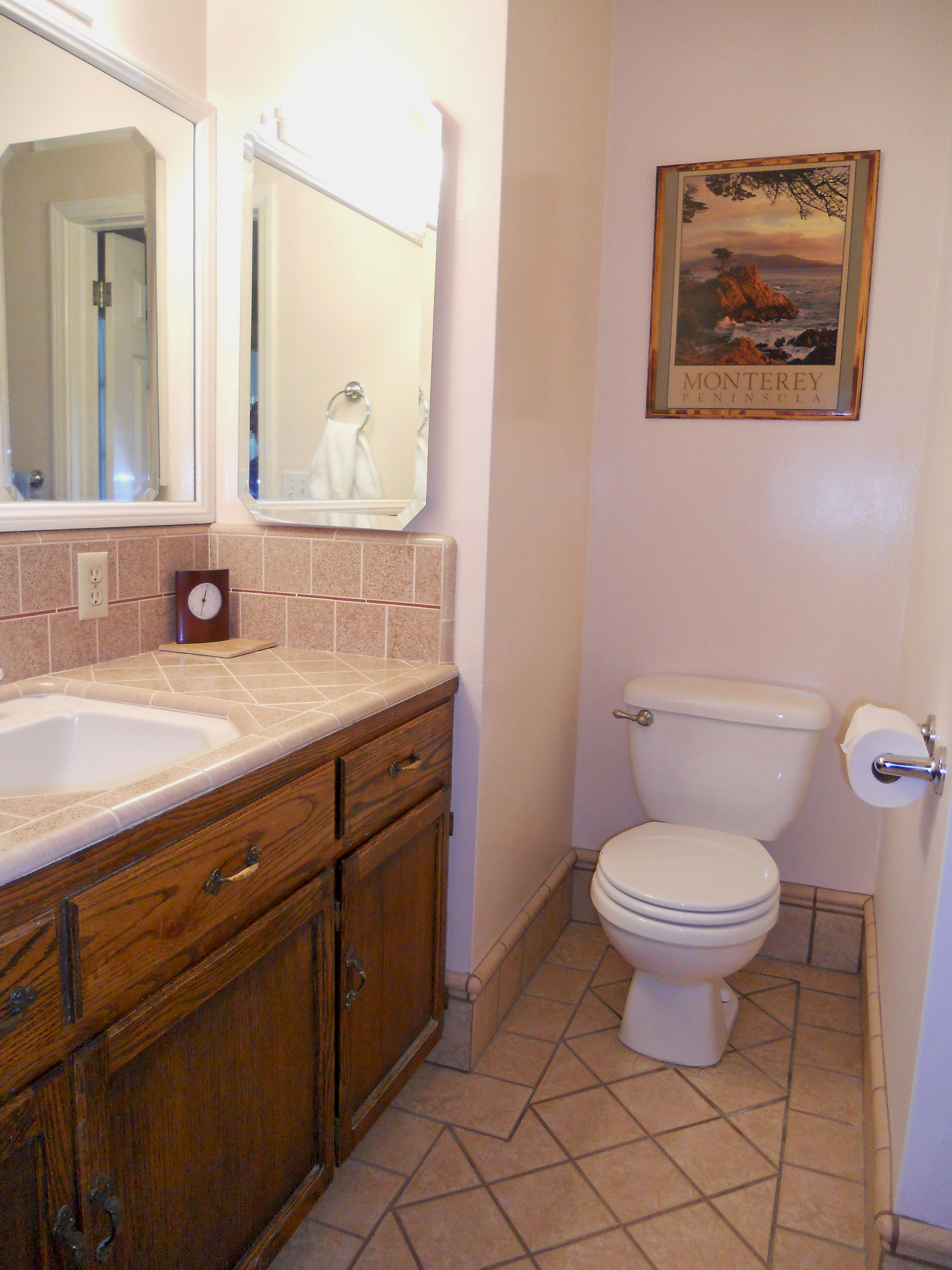 Private master bathroom with original counter top tile in like-new condition, and newer tile flooring.