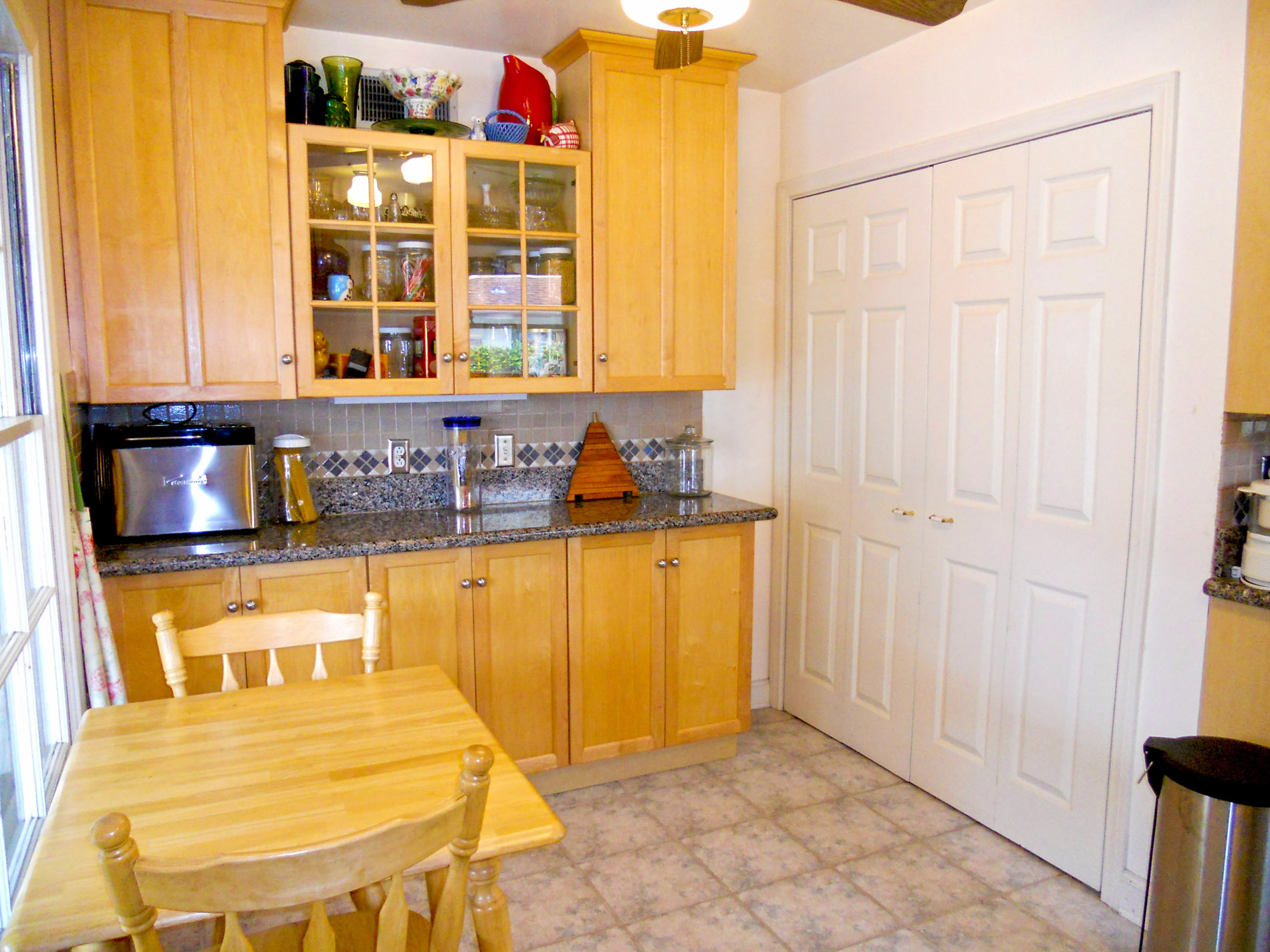 Breakfast nook area with built-in hutch -- laundry behind the folding doors (washer/dryer included with sale).