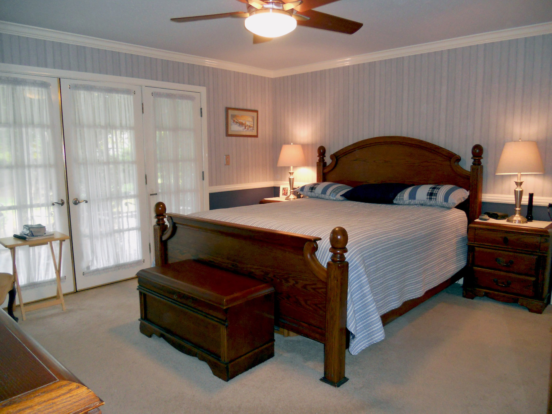 Large master suite with crown molding, carpeting, two closets (one of which is a walk-in), and custom French doors leading to the beautiful backyard!