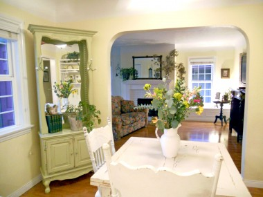 Spectacularly cute formal dining room with arched wall leading into the living room.