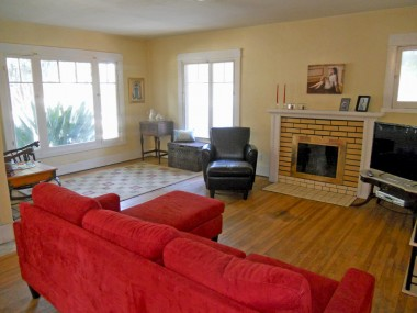 Spacious living room with fireplace, hardwood floors, and lots of natural light.