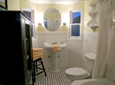 Remodeled bathroom with pedestal sink, charming floor tile, and white cottage-style beadboard.