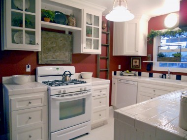 Remodeled kitchen with glass-fronted cabinets, tile counter tops, dishwasher, and gas stove!