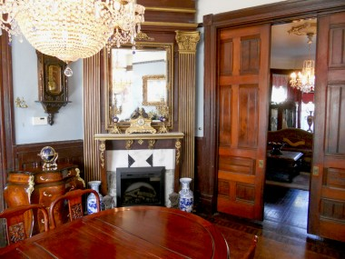 Alternate view of formal dining room with fireplace and pocket doors (which are half open to prove that they still work and are as beautiful as the day they were installed 122 years ago).