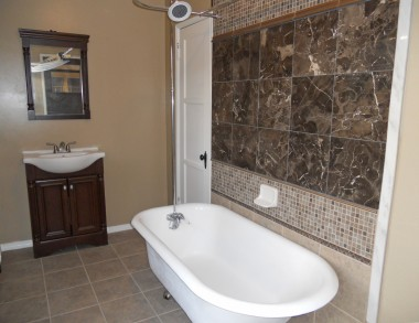Second remodeled bathroom with clawfoot tub, new vanity, and tile floor and backsplash.
