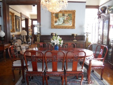 Very large formal dining room with chandelier, original wood floors, picture molding and fireplace.