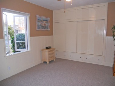 Large front bedroom with expansive closet space, working windows, view of Mt. Rubidoux, ceiling fan, and new carpet!