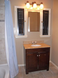 Remodeled hall bathroom with tile floor, new vanity, new toilet, new tub, and original windows.
