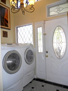 Laundry room off the kitchen with exit door to side yard. Built-in shelving to left of washer/dryer units. Washer/dryer are negotiable items.