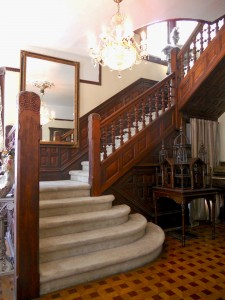 Original carved wood staircase in the foyer.