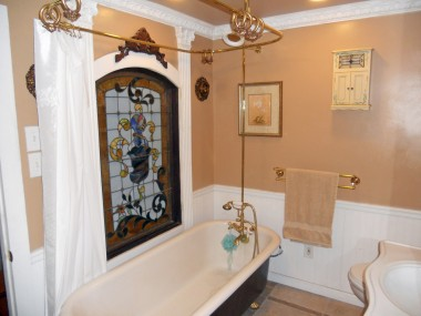Upstairs hallway bathroom with tile floor, original clawfoot tub and a separate shower.