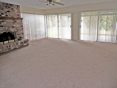 Huge living room with brick fireplace and brand spanking new carpet throughout!!