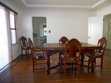 Formal dining room with original hardwood floors and tray ceiling. Prior owner removed French doors; however, this owner has period French doors that are ready to be installed for side patio access.