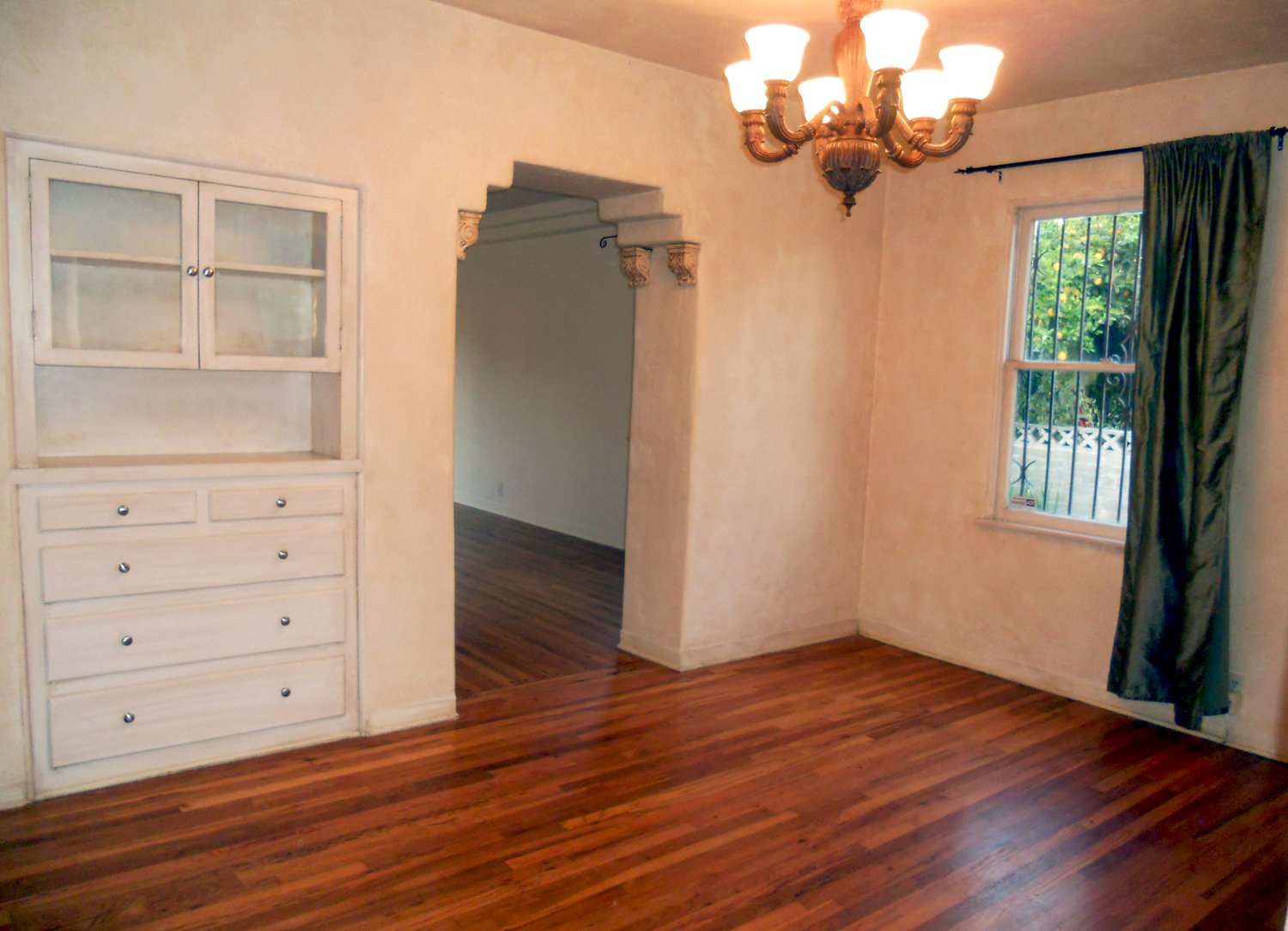 Formal dining room with built-in hutch and original hardwood floors.